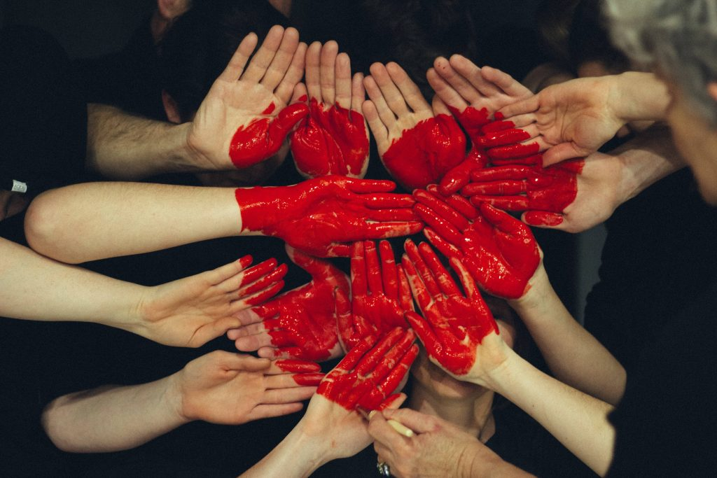 People making a heart symbol with their hands.