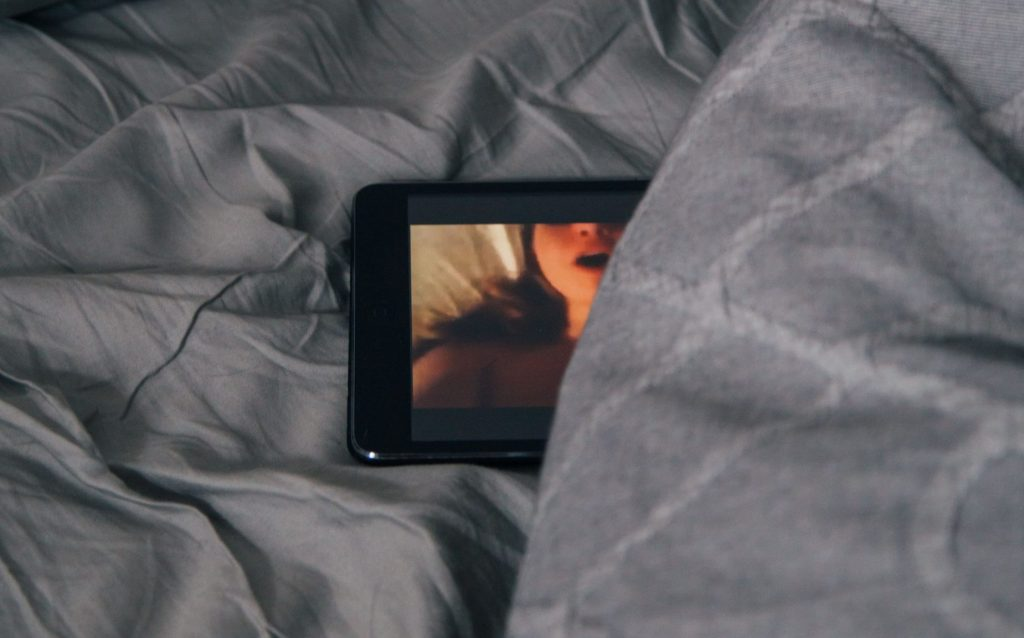 Sexual materials on phone in bed.